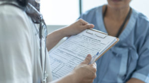 Doctor reviewing a chart while talking to a patient.